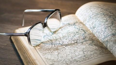 Das Bild zeigt eine Brille, die auf einem geöffnetem Buch liegt.