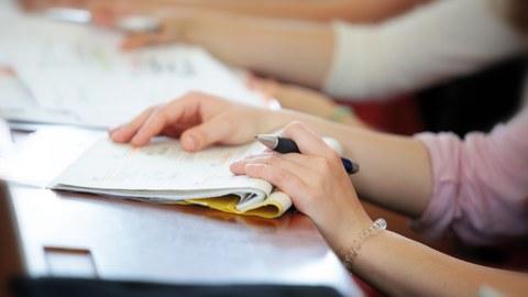 Das Bild zeigt eine Studierende im Hörsaal mit einem Stift und Notizbuch in der Hand.