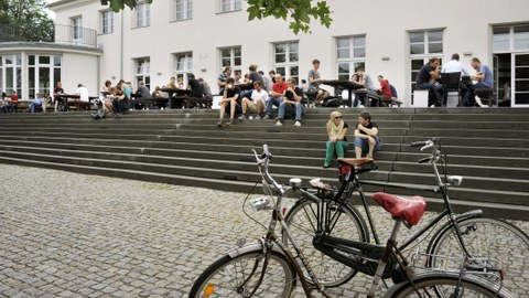 This picture shows two bicycles in the right foreground and the TU Dresden Altmensa in the background with several students sitting on the stairs, having lunch and conversing.