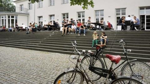 Das Bild zeigt zwei Fahrräder im Vordergrund und mehrere Studierende im Hintergrund, die vor der Alten Mensa sitzen.