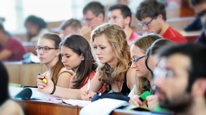 The picture shows students in a lecture hall.