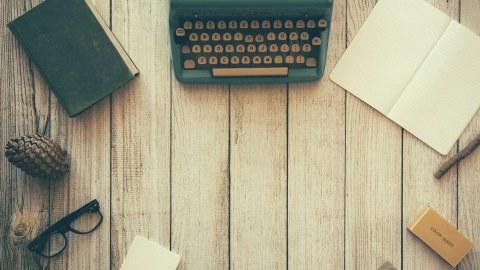 Das Bild zeigt diverse Schreibutensilien, darunter eine Schreibmaschine, ein geschlossenes und geöffnetes Notizbuch sowie eine Brille auf einem Tisch.