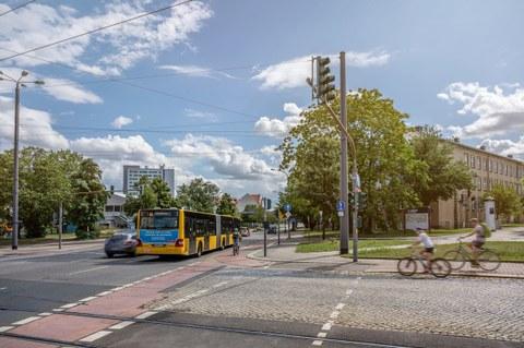 """Foto des Verkehrs auf dem TU-Gelände mit Fahrradfahrern, Autos und dem Bus """"61""""."""