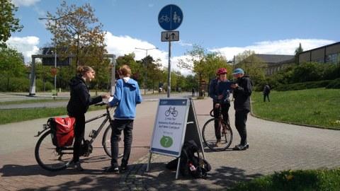 Zu sehen sind zwei Befrager, welche gerade zwei Radfahrende interviewen.