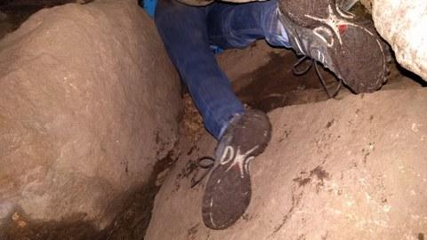 eine suchende Person in einer Höhle