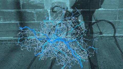 Zu sehen ist eine Heatmap mit den Radverkehrsströmen in Dresden sowie im Hintergrund der Schatten eines Fahrrads