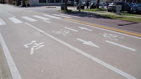 Das Bild zeigt eine Straße in Quartu Sant'Elena, Sardinien. Im Vordergrund wurde ein breiter Fahrbahnstreifen für Läufer abmarkiert. Darauf folgt ein Radfahrstreifen und im Hintergrund eine Fahrspur für den Kfz-Verkehr (Einbahnstraßenregelung).