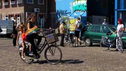 Zu sehen ist eine Straßenszene in der eine Frau auf dem Fahrrad mit Kindersitzen fährt