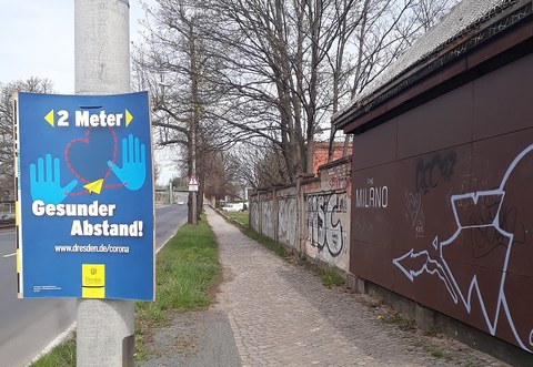 """Poster by the City of Dresden raising awareness to keep a """"healthy"""" distance of 2 meters due to Covid-19, while the sidewalk does not allow pedestrians to keep such a distance."""
