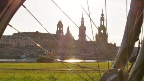 Dargestellt ist eine Silhouette von Dresden (Frauenkirche, Hofkirche) sowie im Vordergrund ein Fahrrad (Deteil des Rads)
