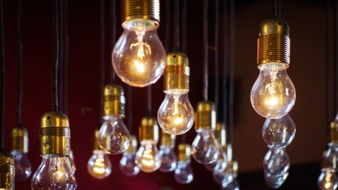 Foto von einer Mehrzahl herunterhängender Glühbirnen. Einige leuchten, andere nicht.