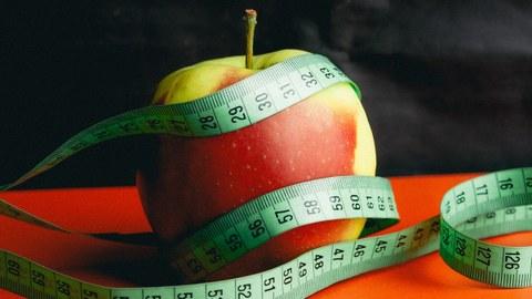 Das Foto zeigt einen Apfel, der von einem Maßband eingekreist ist.