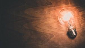 Das Foto zeigt eine leuchtende Glühbirne auf einer hölzernen Oberfläche.
