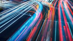 Foto: Bunte Verkehrslichter auf einer großen vielbefahrenen Straßenkreuzung in Zeitraffer bei Nacht.
