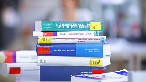 Ein Stapel Bücher liegt auf einem Tisch in der Bibliothek.