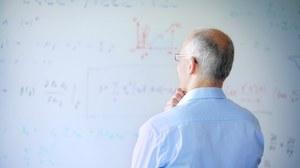 Ein älterer Mann steht nachdenklich vor einem mit Formeln beschriebenen Whiteboard.