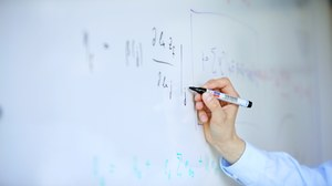 Mit einem Stift werden Formeln an ein Whiteboard geschrieben.
