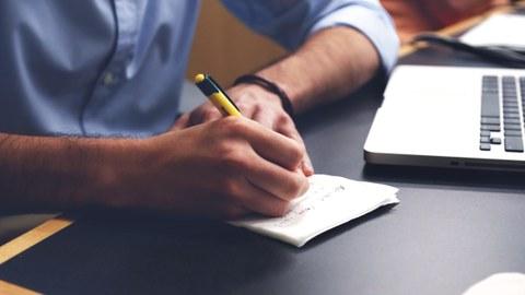 Ein Studierender sitzt an einem Laptop und macht sich Notizen auf einem Block.