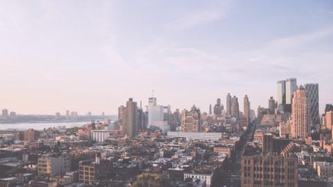 Dargestellt ist die Ansicht einer Stadt mit Skyline im Hintergrund.