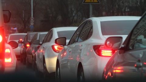 Auto-Stau: mehrere Autos stehen hiontereinander dicht an dicht. Ihre Rücklichter und teilweise Bremslichter sind an.