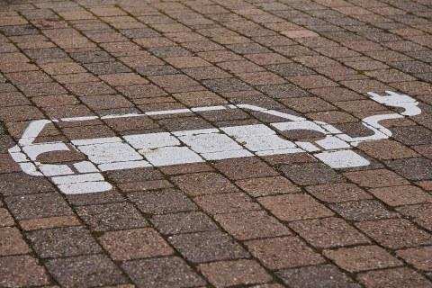 gekennzeichneter Parkplatz für ein E-Auto zum Aufladen. Pflastersteine. Daauf ist mit weißer Farbe ein Auto mit einem Kabel gemalt.