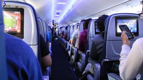 Foto: Innenraum eines Flugzeugs. Blick den Gang entlang. Links und rechts sitzen Passagiere. Einige schauen auf ihr Handy. Andere blicken auf Bildschirme in der Sitzlehne des Platzes vor ihnen.