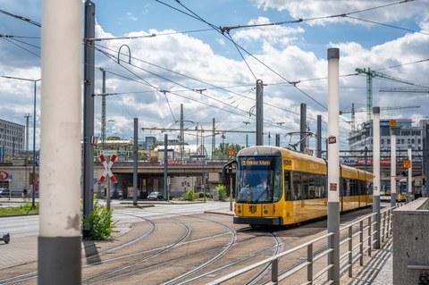 Eine gelbe Dresdner Straßenbahn hält an einer Haltestelle.