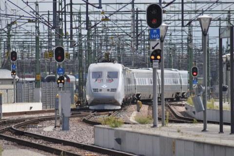 Ein Intercity Zugfährt durch eine Gegend mit vielen Hochspannungsleitungen
