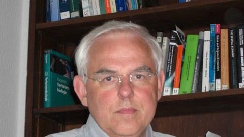 Porträt von Prof. Johannes Bröcker. Er sitz vor einem Bücherregal.