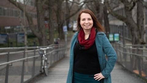 Porträt von Angela Francke, im mantel und mit Schal. Im Hintergrund ein herbstlicher Park.