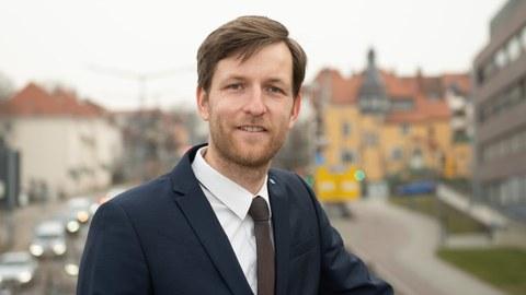 Pascal Kerschke im halbporträt draußen. Im Hintergrund eine Stadt.