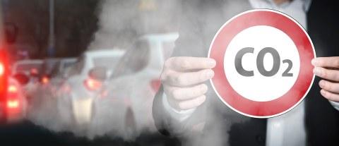 Eine Person hält ein rundes Straßenschild. Es ist Rot umrandet und in der Mitte steht CO2. Im Hintergrun ist ein Stau und Abgase.