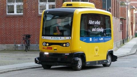 Ein kleiner gelber Bus der Berliner Verkehrsbetriebe, der autonom fährt.