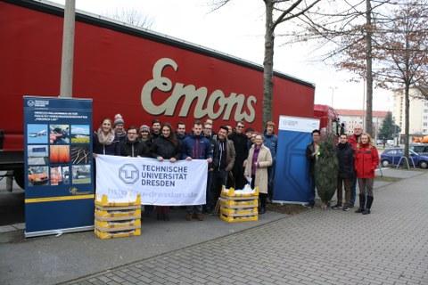 Studentengruppe mit den zu verladenden Stollen vor dem Container