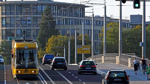 Stadtverkehr in Dresden, eine Straßenbahn fährt auf einer Brücke daneben Autos und auf dem Fußweg Personen