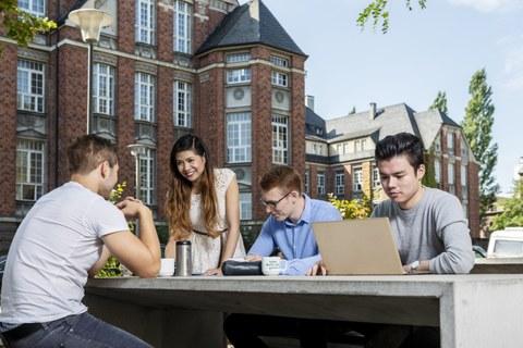 vier internationale Studierende sitzen vor der Biomensa mit Laptop. Sie unterhalten sich und lernen.