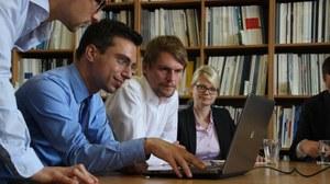 Vier Personen betrachten den Monitor eines Laptops