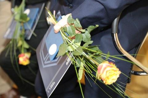 Ein Absolvent hält eine Zeugnismappe und eine Rose in der Hand