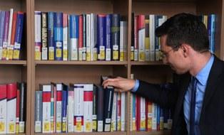 Ein Forscher entnimmt ein Buch aus einem Bücherregal