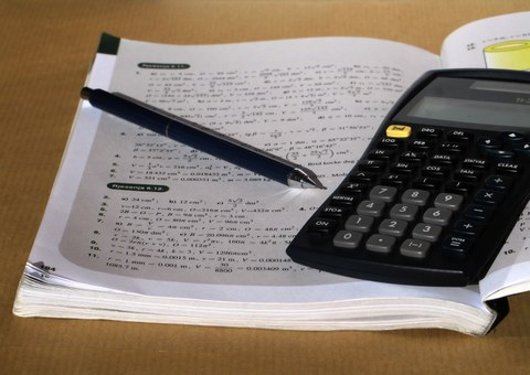 Picture of an opened exercise book together with a calculator and a pen