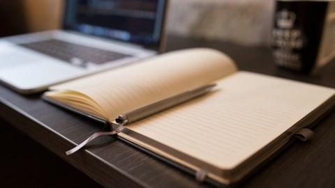 Ein leeres Notizbuch liegt auf einem Tisch, auf dem ein Laptop und eine Tasse steht.