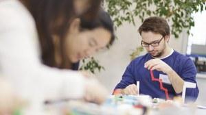 Studierende sitzen an einem Tisch und arbeiten