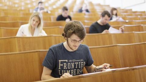 Ein Student sitzt im Hörsaal während einer Prüfung