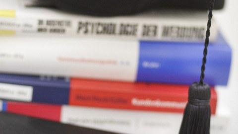 Eine Dissertation liegt neben verschiedenen gestapelten Büchern, auf denen eine Abschlussmütze platziert ist
