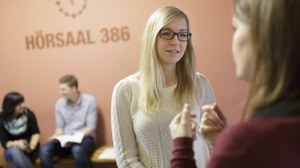 Zwei Studentinnen sprechen vor dem Hörsaal 386 im Hülsse-Bau miteinander
