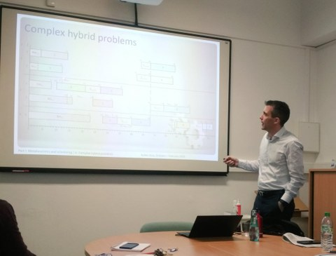 A man (Ruben Ruiz Garcia) gives a lecture and points to the presentation with a pointer.