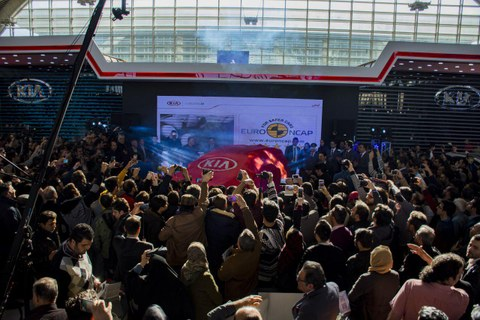 Crowd in front of a car in an exhibition hall.