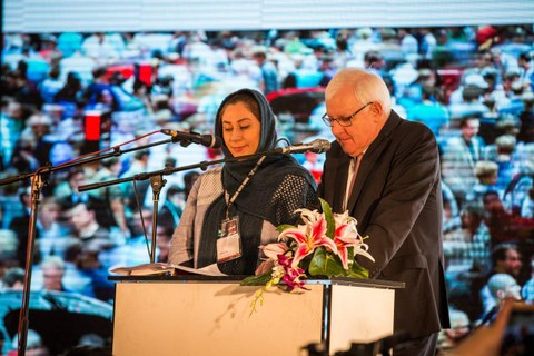 A man and a woman with a headscarf stand at a lectern and give a speech.