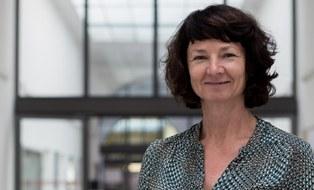 Hier ist ein Bild der Sekretärin Evelyn Krug. Sie lächelt.