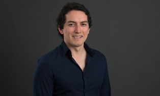 Hier ist ein Bild von Eduardo Alarcon. Er lächelt.